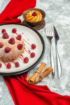 Вид снизу ягодный торт на белой овальной тарелке, красная шаль, бисквитная вилка и обеденный нож на серой поверхности