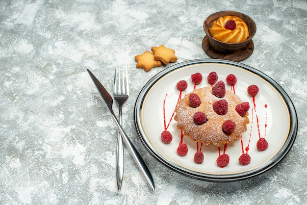 Bottom view berry cake on white oval plate biscuits crossed fork and dinner knife on grey surface free space