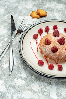 Bottom view berry cake on white oval plate crossed fork and dinner knife on grey surface