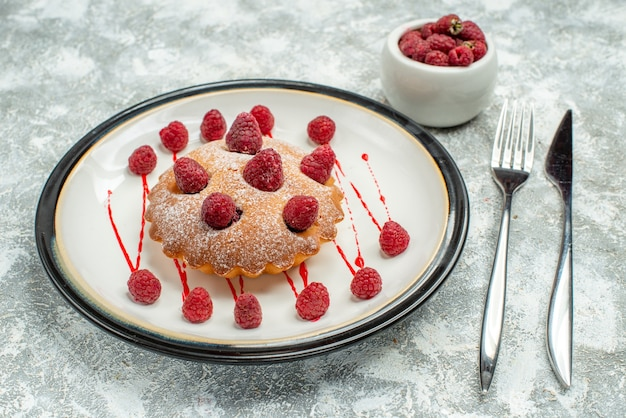 Bottom view berry cake on white oval plate raspberries in bowl fork and dinner knife on grey surface