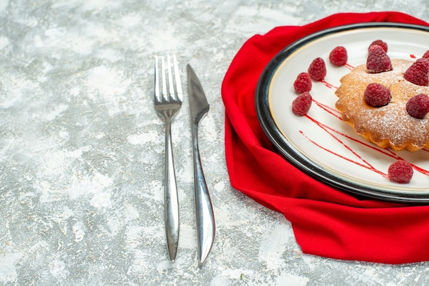 Bottom view berry cake on white oval plate red shawl fork and dinner knife on grey surface free space