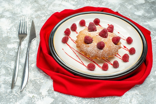 Bottom view berry cake on white oval plate on red shawl fork and dinner knife on grey surface