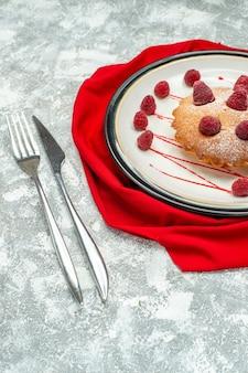 Torta di bacche vista dal basso su piatto ovale bianco su forchetta scialle rossa e coltello da pranzo su superficie grigia