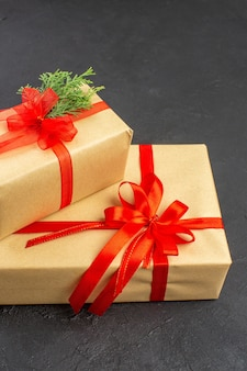 Bottom view big and small xmas gifts in brown paper tied with red ribbon branch fir on dark background
