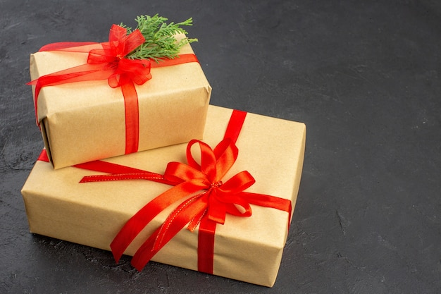Vista dal basso regali di natale grandi e piccoli in carta marrone legati con nastro rosso su spazio libero scuro