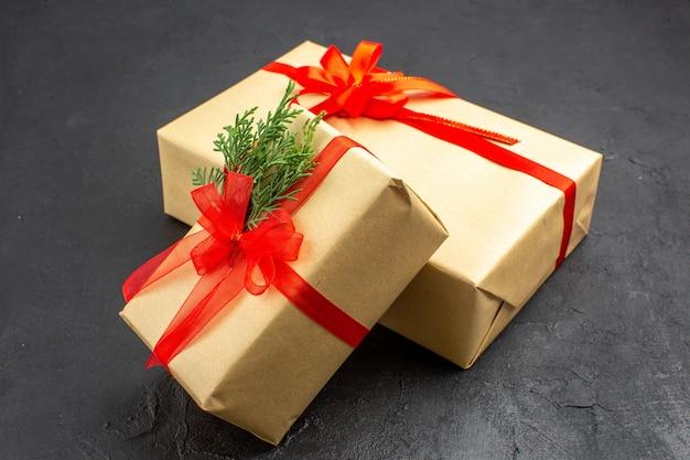 Vista dal basso regali di natale grandi e piccoli in carta marrone legati con nastro rosso su oscurità