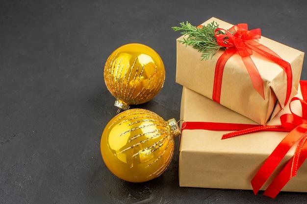 Vista dal basso regali di natale grandi e piccoli in carta marrone legati con palline di natale con nastro rosso su sfondo scuro