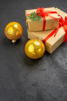 Vista dal basso regali di natale grandi e piccoli in carta marrone legati con palline di natale con nastro rosso su spazio libero scuro