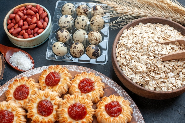 Bottom view biscuits with jam on platter oats in bowl wheat spikes quail eggs in viol peanuts in bowl on dark background
