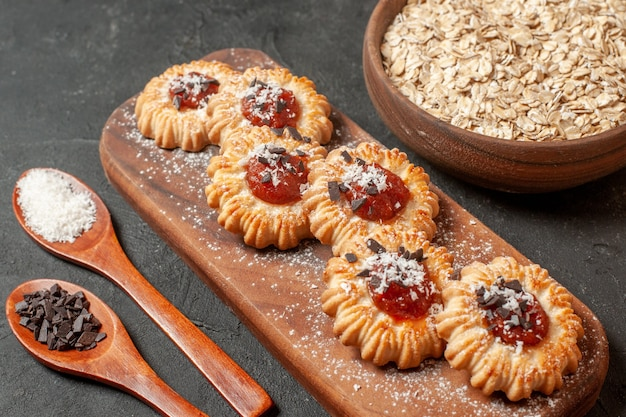 Bottom view biscuits with jam on wood board coconut powder and chocolate powder in wooden spoons oats in wooden bowl on dark background
