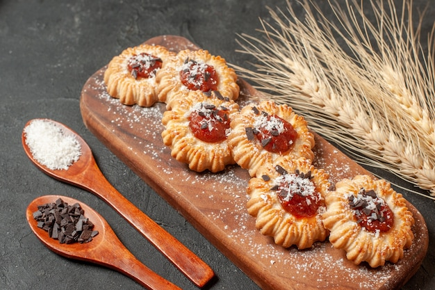 Bottom view biscuits with jam on wood board coconut powder and chocolate powder in wooden spoons wheat spikes on black background