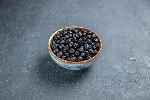 Bottom view black currant in bowl on dark surface free space