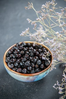 Bottom view black currant in bowl dried flowers on isolated surface