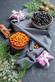 Bottom view black currant sea buckthorn in bowls pine branches purple shawl cinnamon on dark surface
