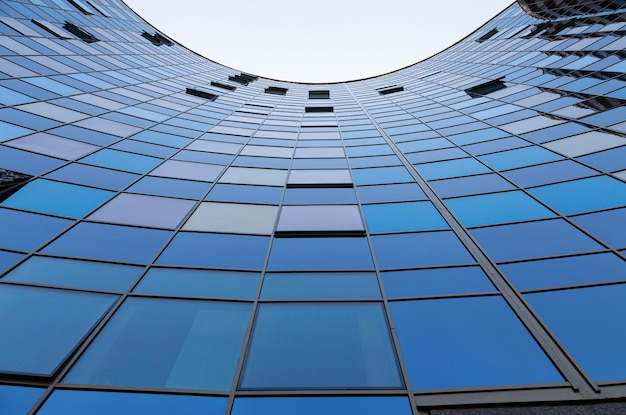 Bottom view of blue glass surface of semicircle building front wall reflecting blue sky