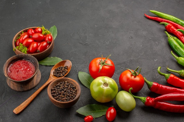 Vista dal basso una ciotola di pomodorini peperoni rossi e verdi caldi e pomodori foglie di alloro ciotole di ketchup e pepe nero e un cucchiaio sulla tavola nera