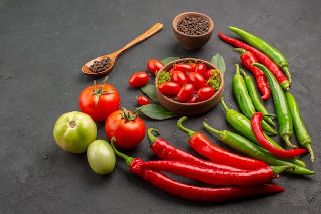 Vista dal basso una ciotola di pomodorini piccanti peperoni rossi e verdi e pomodori pepe nero in un cucchiaio di legno una ciotola di pepe nero su sfondo nero
