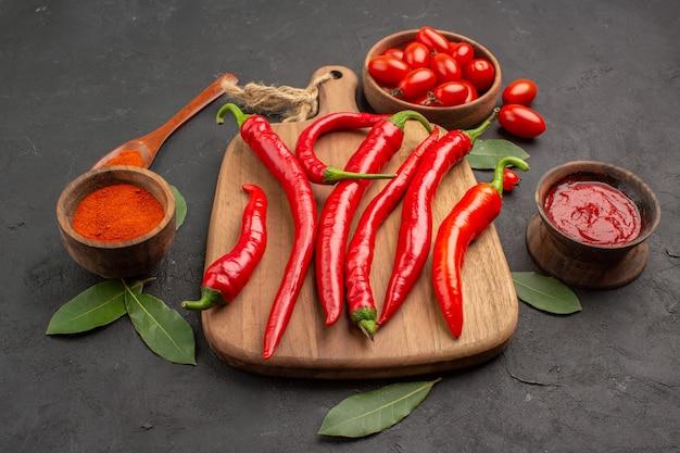 Vista dal basso una ciotola di pomodorini peperoni rossi piccanti sul tagliere un cucchiaio di legno foglie di alloro e ciotole di ketchup e peperoncino in polvere sulla tavola nera