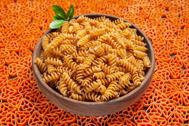 Bottom view a bowl of spirali pasta on heart shaped italian pasta on dark surface