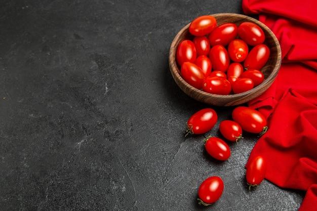Ciotola di vista dal basso con un asciugamano rosso di pomodorini su sfondo scuro