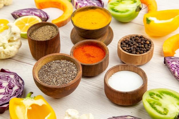 향신료와 함께 밑면 그릇 잘라 피망 콜리 플라워 잘라 호박 잘라 붉은 양배추 흰색 테이블에 녹색 토마토를 잘라