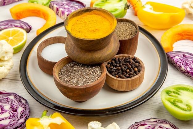 Ciotole vista dal basso con spezie su piatto rotondo curcuma sale pepe nero pepe rosso in polvere verdure tagliate su superficie bianca white