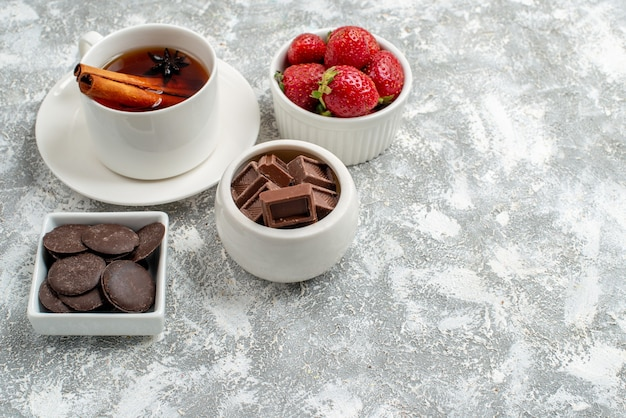 Bottom view bowls with strawberries and chocolates and cinnamon anise seed tea at the top left of the grey-white background