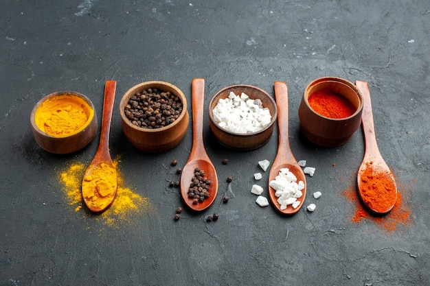 Bottom view bowls with turmeric black pepper sae salt red pepper powder wooden spoons on black surface