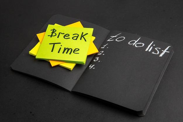 黒いテーブルの黒いメモ帳のリストを行うために付箋に書かれた底面図の休憩時間