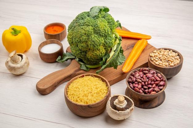 Vista dal basso broccoli tagliati carota sul tagliere sale pepe rosso peperone ciotola con tubi di pasta sottili fungo sul tavolo grigio