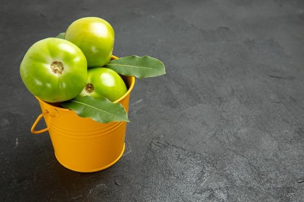 Vista dal basso secchio di pomodori verdi e foglie di alloro sulla destra dello sfondo scuro
