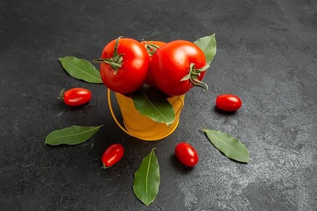 Vista dal basso un secchio con pomodori intorno a pomodorini e foglie di alloro su sfondo scuro