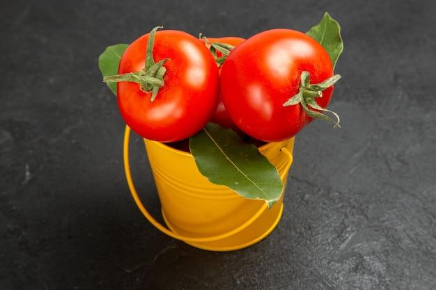Vista dal basso un secchio con pomodori e foglie di alloro su sfondo scuro