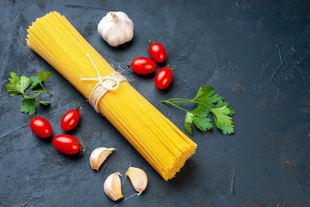 Vista dal basso fascio di sphaggeti pomodorini aglio prezzemolo sul tavolo scuro posto copia