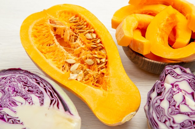 Bottom view butternut squash in bowl half red cabbage and half squash on grey wooden table