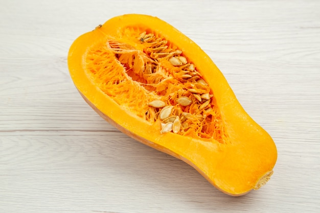 Bottom view butternut squash cut in half on white wooden table free space