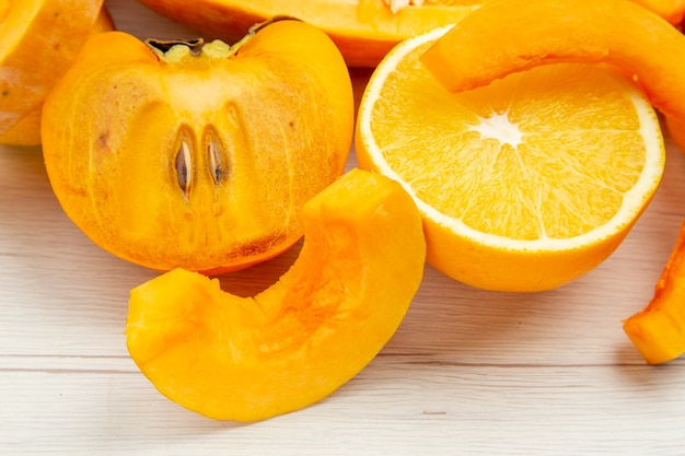 Vista dal basso zucca tagliata cachi arancioni sul tavolo bianco