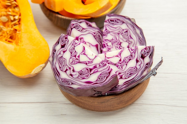 Bottom view butternut squash squash slices in bowl cut red cabbage in bowl on grey wooden table
