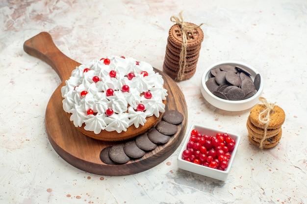 Torta vista dal basso su ciotole con frutti di bosco e biscotti al cioccolato legati con una corda sul tavolo grigio chiaro