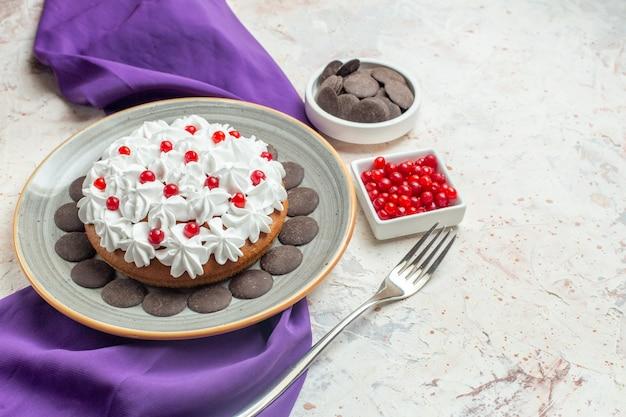 Torta vista dal basso con crema pasticcera e cioccolato su piatto ciotole di scialle viola con cioccolato e forchetta di frutti di bosco su superficie bianca