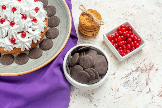 Bottom view cake with pastry cream on grey plate purple shawl cookies tied with rope berries and chocolate in bowl on white table
