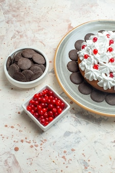 Bottom view cake with pastry cream on oval plate berries and chocolate in bowls on beige table
