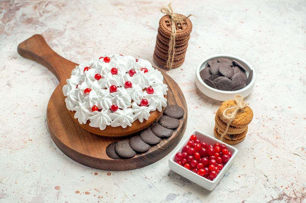 Bottom view cake with white cream on wooden cutting board bowls with berries and chocolate cookies tied with rope on light grey table