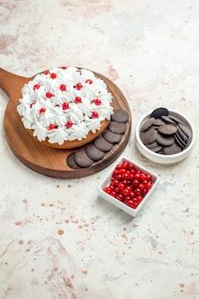Torta vista dal basso con crema pasticcera bianca e cioccolato su tagliere ciotole con frutti di bosco e cioccolato su superficie grigio chiaro