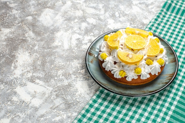 Bottom view cake with white pastry cream and lemon slices on round plate on green and white checkered table