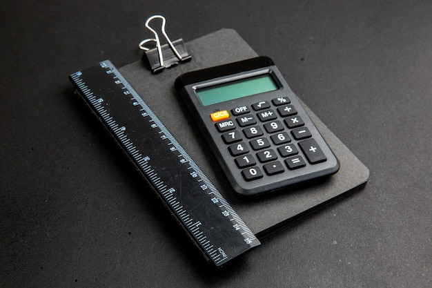 Bottom view calculator and ruler on notepad on dark table