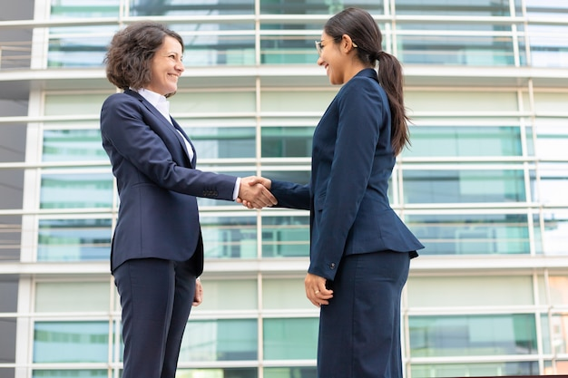 Bottom view of cheerful colleagues shaking hands near building. young women wearing formal suits meeting outdoor. business handshake concept
