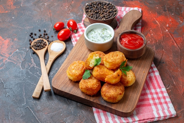 Bottom view cheese balls sauces in bowls on wood board cherry tomatoes wooden spoons black peppers on dark background