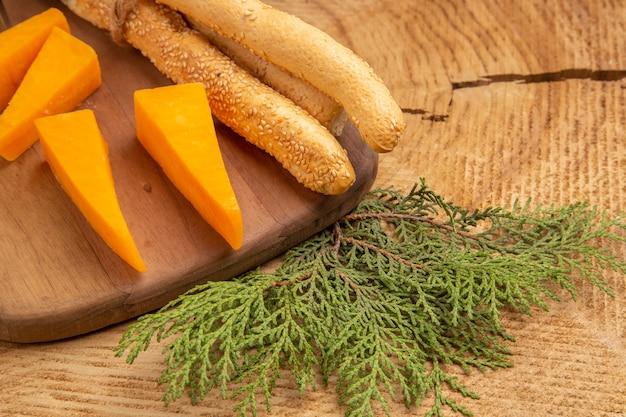 Vista dal basso formaggio e pane su tagliere rami di pino su tavola di legno