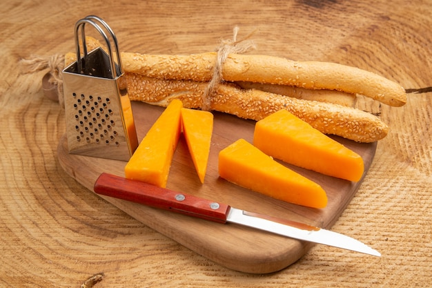 Bottom view cheese and bread knife small grater on cutting board on wooden surface